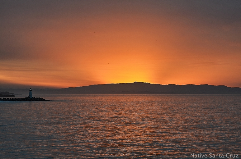 The sun rises from behind Toro Peak, turning the Monterey Bay a golden orange.